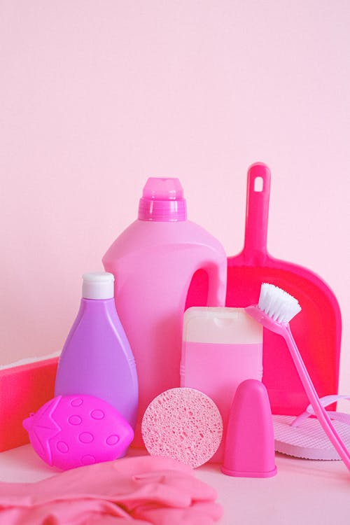 Set of assorted plastic containers with gloves brush and scoop for cleaning routine on pink background