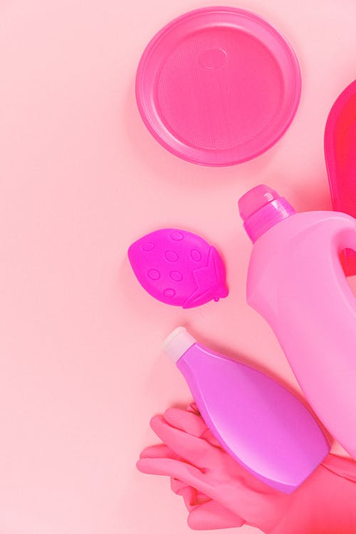 Top view of composed bottles and cup lid with rubber gloves on pink background