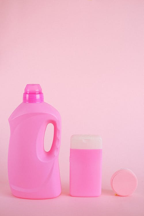 Collection of assorted plastic containers in different shape for various products placed on pink background