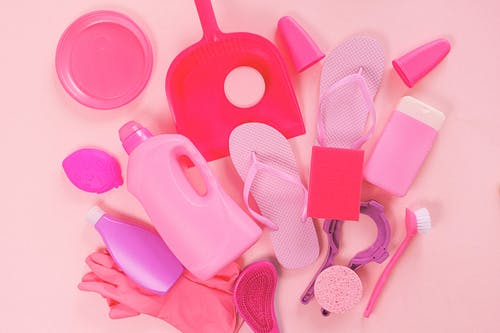 Collection of various plastic detergent bottles and cleaning tools placed on pink background near flip flops and rubber gloves