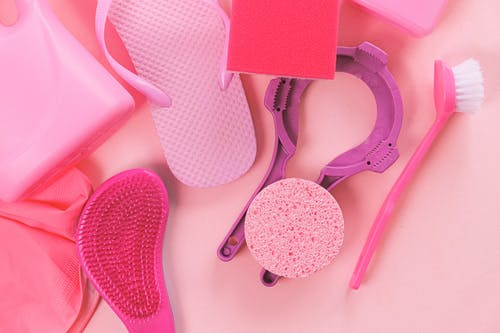 Overhead layout of assorted cleansing tools including brush sponge and plastic bottle arranged on light pink surface