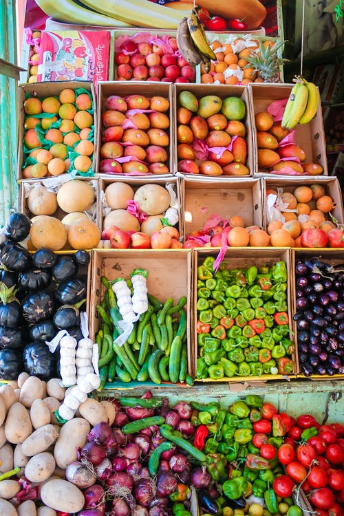 Fresh exotic fruits and vegetables placed on counter in market stall at daytime