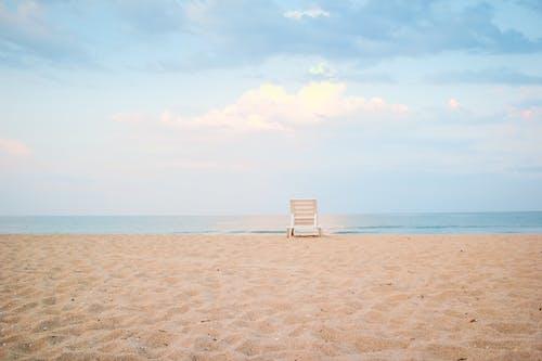 Sunbed placed on sandy beach