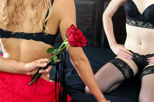 Woman in Black Tube Top and Black Skirt Holding Red Rose