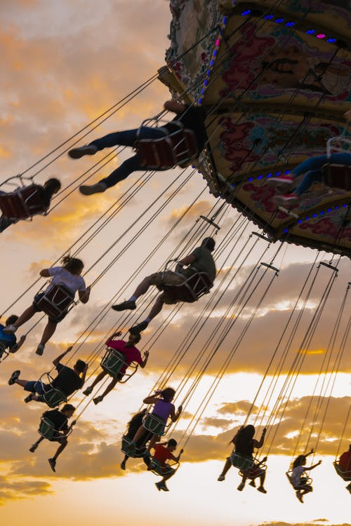 People having fun on swing chain carousel in amusement park against colorful sky at sunset