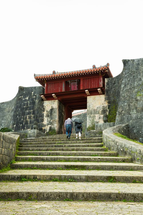 From below back view of unrecognizable couple of tourists walking on staircase near old stone castle in Japan