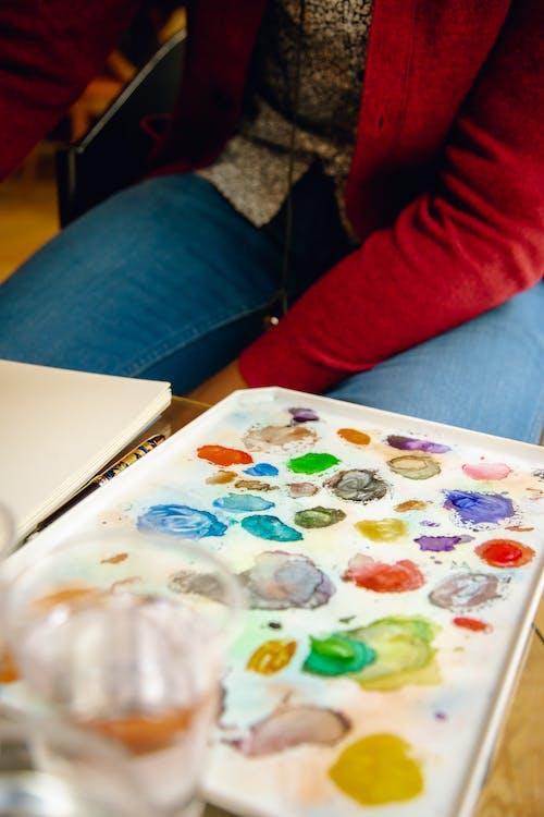 Crop artist near colorful paint palette in workshop