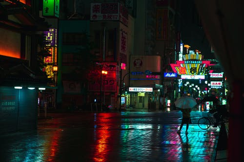 Anonymous person with umbrella on sidewalk near shiny buildings in town at dusk in rainy weather