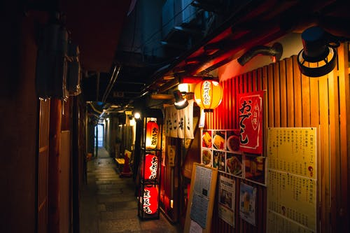 Narrow street with traditional Japanese izakaya bars decorated with hieroglyphs and traditional red lanterns in evening