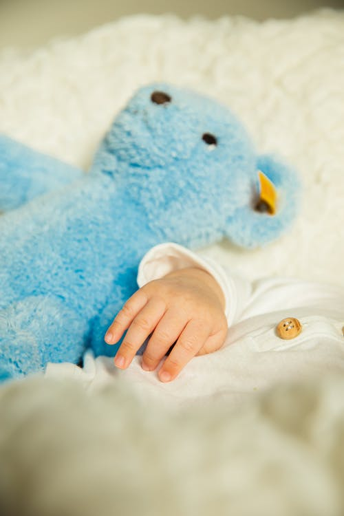 From above of crop unrecognizable baby in white pajama lying on soft bed with blue plush toy in daylight