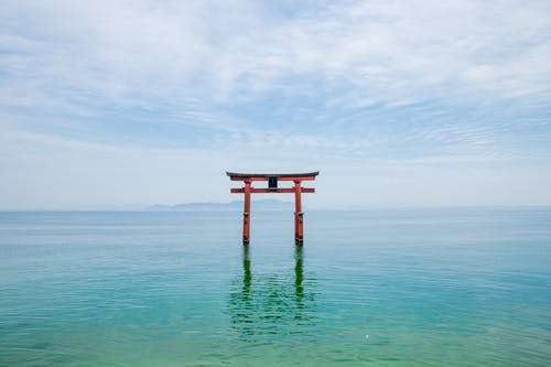 Picturesque scenery of torii of ancient Shirahige Shrine in Biwa Lake against cloudy blue sky in Takashima