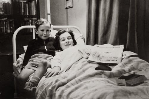 Grayscale Photo of A Boy Sitting Beside His Mother Lying On A Hospital Bed