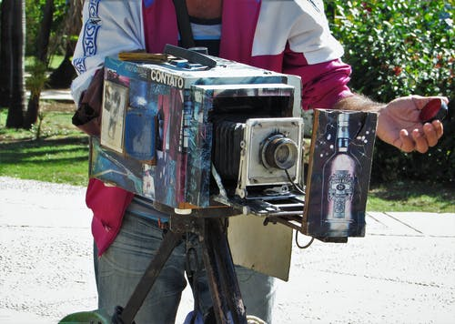 Person Holding Silver and Black Vintage Camera