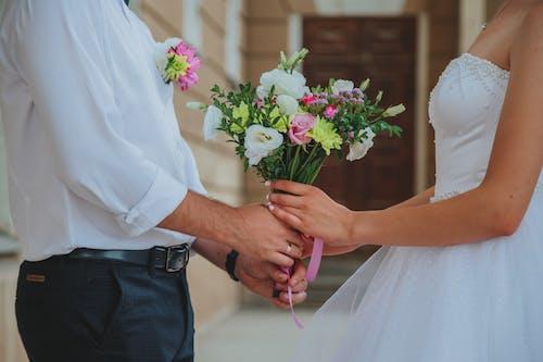 Newlyweds holding bouquet of wedding flowers