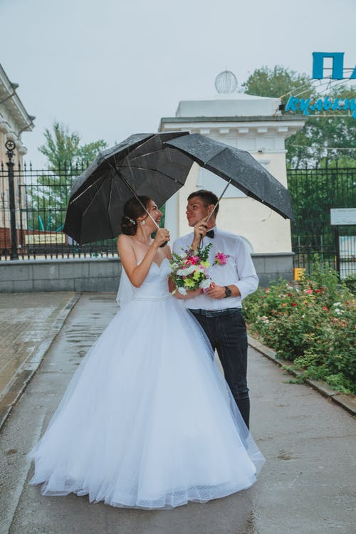 Full body of happy groom and bride in wedding outfit with bouquet of flowers looking at each other while standing on pavement under umbrellas in rainy weather