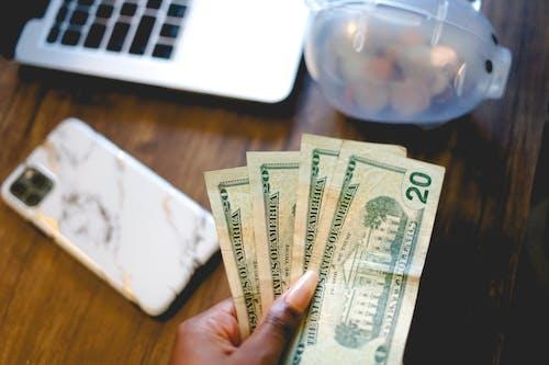 Person Holding 20 US Dollar Bills near the Piggy Bank