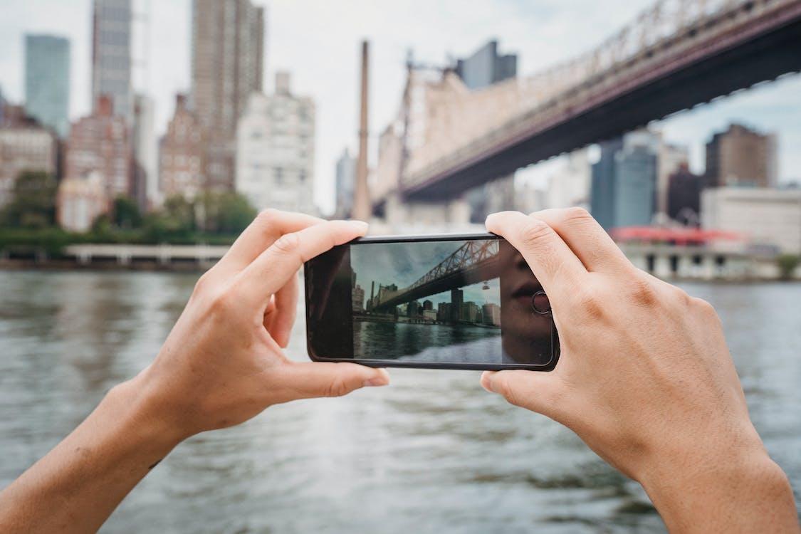 Crop unrecognizable traveler taking photo of modern suspension bridge in city using mobile phone in daytime
