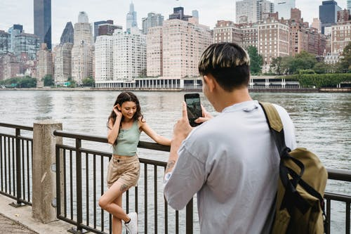 Young man photographing girlfriend on smartphone during date in city downtown near river