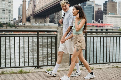 Stylish diverse couple holding hands and strolling on city promenade under bridge over river