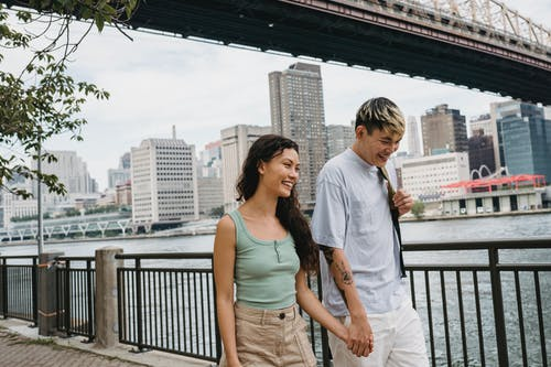 Cheerful young ethnic couple holding hands and walking near river in downtown