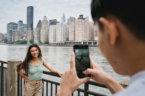 Crop male taking photo of smiling ethnic girlfriend on city embankment against modern skyscrapers