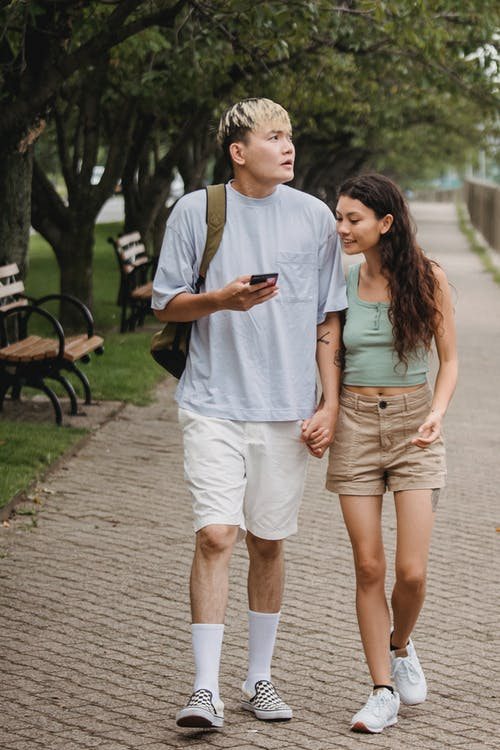 Loving ethnic couple walking along park alley and using smartphone
