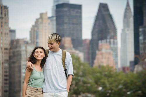 Delighted young ethnic couple cuddling while standing against scenic cityscape with modern skyscrapers