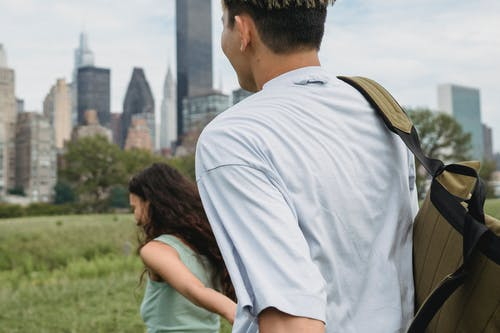 Crop smiling couple holding hands on meadow in city