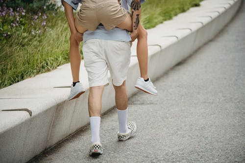 Back view of crop anonymous male carrying female partner while walking on asphalt pavement in city