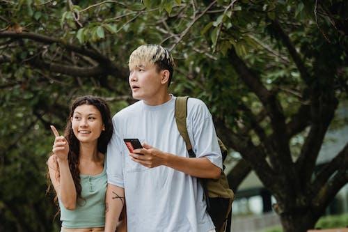 Feliz Mujer étnica Cerca De Novio Asiático Con Smartphone En El Parque