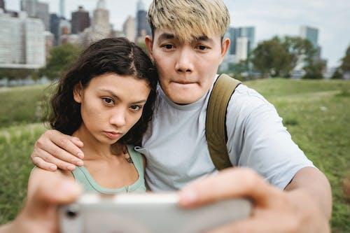 Crop focused multiracial couple taking selfie on smartphone in town