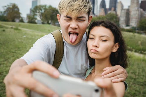Crop diverse couple grimacing while taking selfie on smartphone