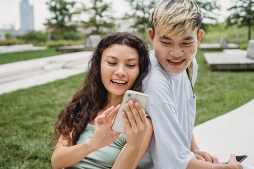 Happy ethnic woman sharing smartphone with crop Asian boyfriend