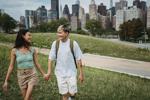 Happy multiethnic couple holding hands on meadow in town