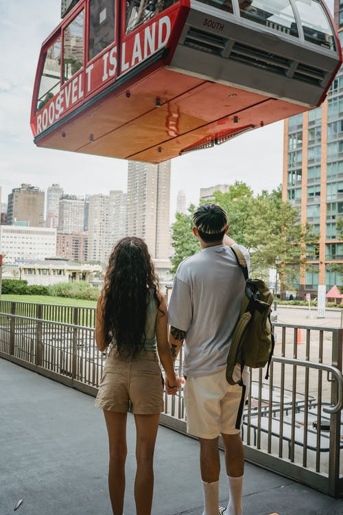 Back view of anonymous couple holding hands on fenced pavement near ropeway and urban buildings