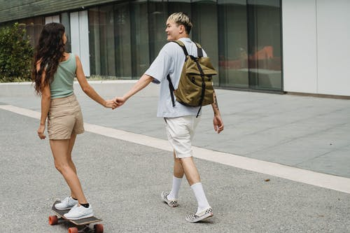Back view of smiling ethnic male with backpack holding hand of anonymous female beloved skateboarding on pavement while looking at each other