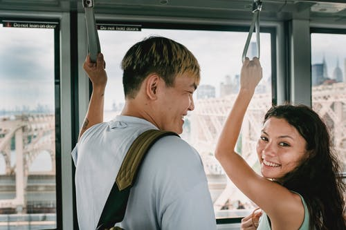 Young happy multiethnic tourists laughing in cable car with raised arms while traveling together