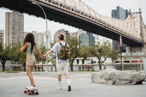 Faceless woman on skateboard holding hand of boyfriend on pavement