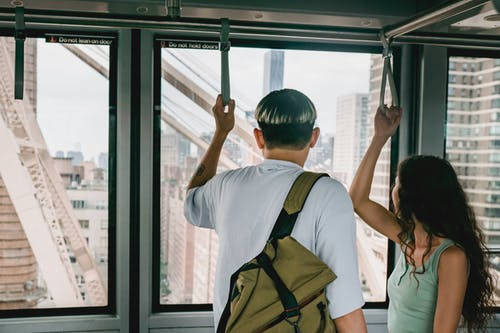 Back view faceless couple in casual clothes riding funicular cabin and grabbing hangers while looking away on urban city views