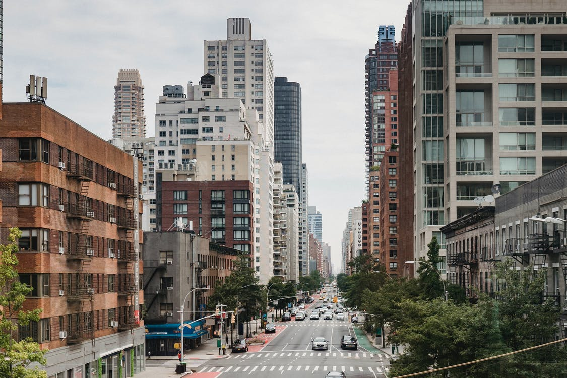 New Your City street with vast busy road between contemporary typical buildings on clear day