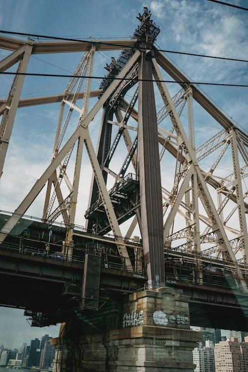 Contemporary cantilever bridge located over river in urban big city under blue sky