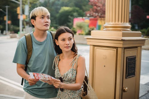 Cheerful Asian couple with map navigating in city