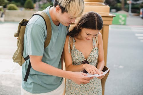 Content young Asian couple in casual wear traveling in new city and checking direction in paper map