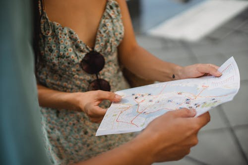 Crop anonymous couple travelers in summer clothes checking location in paper map while walking in unknown city