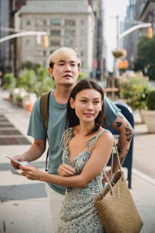 Positive multiracial couple checking direction in map while having trip together in city center