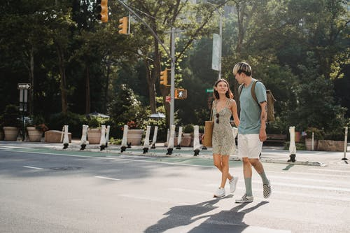 Full body of happy young girlfriend carrying bag while walking on asphalt crosswalk with boyfriend