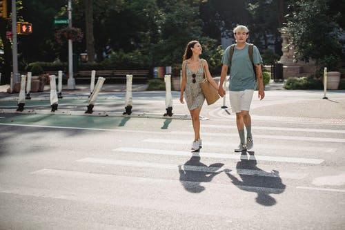 Young stylish diverse couple holding hands while walking on crosswalk