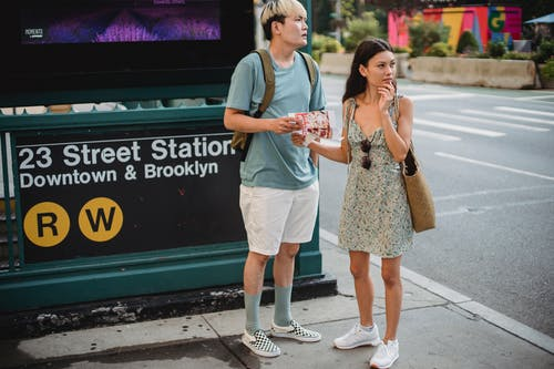Full body of diverse couple standing with map while trying to find direction in city center during trip