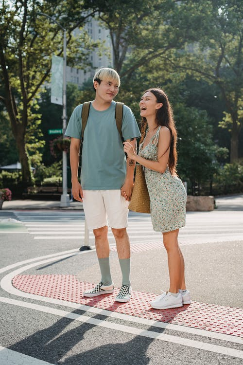 Young smiling diverse couple standing on crosswalk