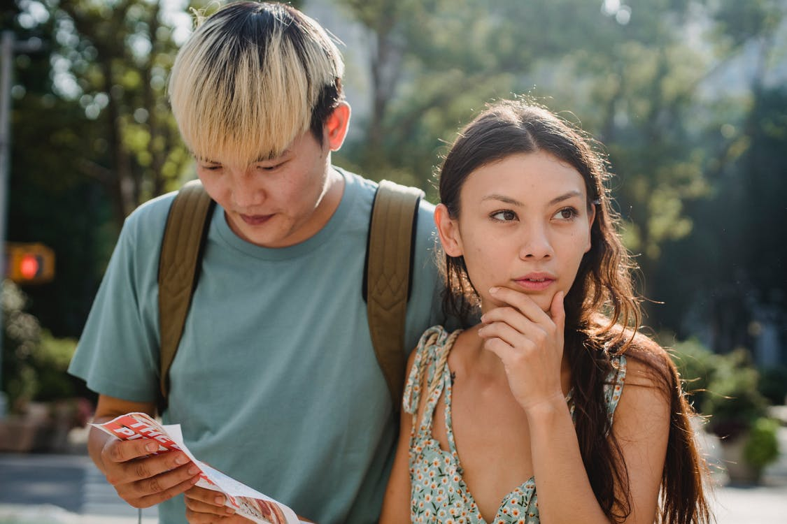 Confused multiracial couple searching way in map while discovering city together during summer holidays